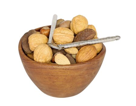 Wooden bowl of various nuts and nutcracker isolated on white photo