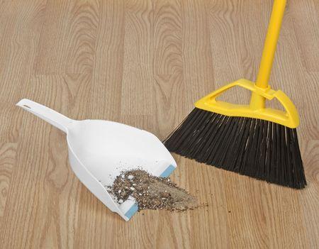 brooms: Broom sweeping up dirt into dust pan on hardwood floor