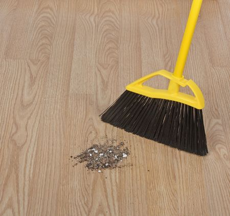 Broom sweeping dirt on a hardwood floor Reklamní fotografie