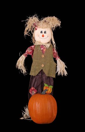Autumn straw girl doll with pumpkin isolated on black photo