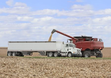 Loading corn from a combine into a truck in a farm field photo