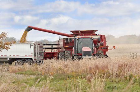 Red combine loading corn into a truck in a farm field photo
