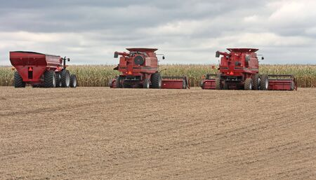 combines: Two combines and a tractor in a farm field