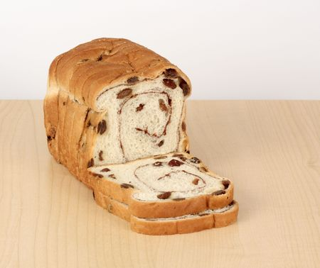 Loaf of sliced raisin bread on a wood table