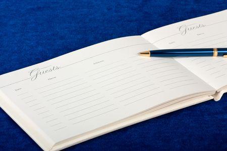 anagrafica: Libro degli ospiti di nozze aperto con una penna su sfondo blu Archivio Fotografico