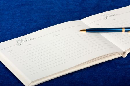 registry: Opened wedding guest book with a pen on a blue background