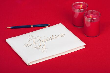 Wedding guest book with pen and candles on a red background photo