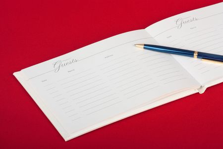 Opened wedding guest book with a pen on a red background photo