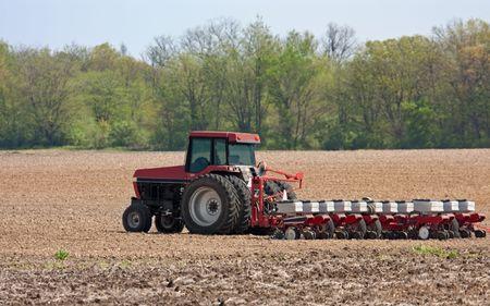 Farm tractor planting corn in a field photo