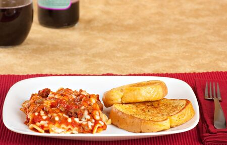 Lasagna and garlic bread on a plate with wine in the background