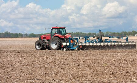 Farm tractor planting corn in a field