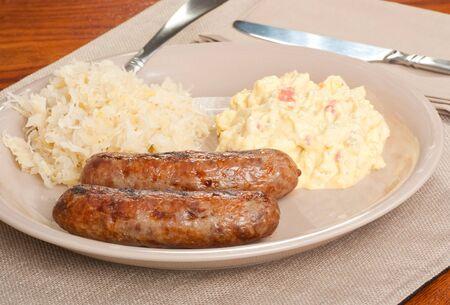 Two bratwursts on a plate with potato salad and sauerkraut Standard-Bild