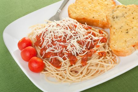Spaghetti topped with sauce and grated cheese with garlic toast and cherry tomatos