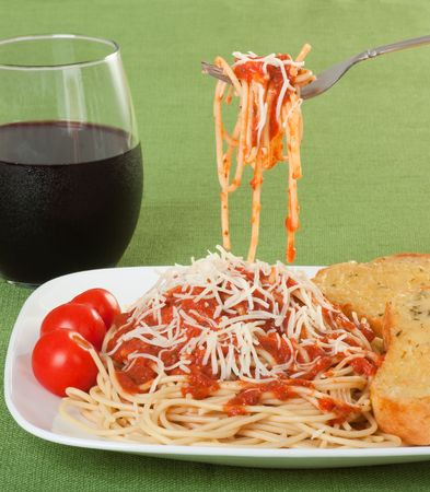 Spaghetti topped with sauce and grated cheese with garlic toast, cherry tomatos and a glass of wine Stock Photo