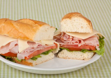 Ham and swiss cheese sub sandwich with lettuce and tomato on a bun