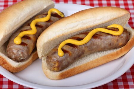 bratwurst: Two bratwurst on a bun with mustard