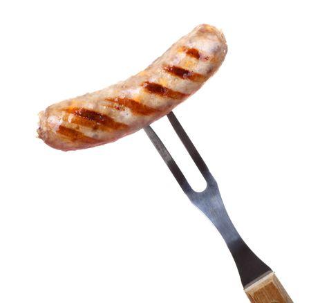 chorizos asados: Bratwurst a la parrilla en una horquilla de barbacoa aislado en blanco  Foto de archivo