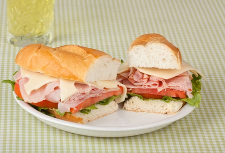 Ham and swiss cheese sub sandwich with lettuce and tomato and a drink photo