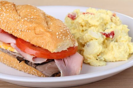 Sub sandwich with roast beef, ham, cheese and tomato along with potato salad photo