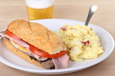Ham and roast beef sub with tomatoes and cheese on a sesame seed bun with potata salad and a beer photo