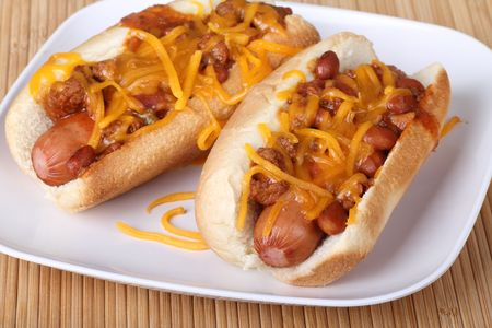 Two hot dogs on a bun covered with chili and melted shredded cheese photo