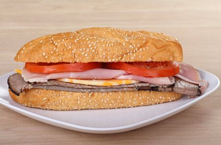 Ham and roast beef sub with tomatoes and cheese on a sesame seed bun Stock Photo - 7633643