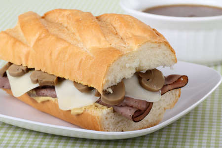 French dip made with roast beef, mozzarella cheese, mushrooms on french bread with au jus photo