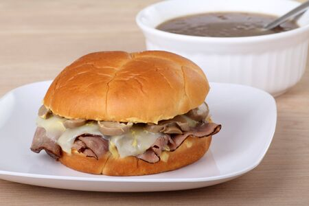 Roast beef with melted mozzarella cheese and mushrooms on a bun with soup in background