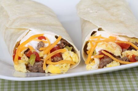 tortillas: Breakfast burritos made with sausage, scrambled eggs, cheese, tomatoes wrapped in tortillas