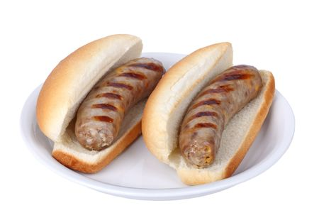Two grilled bratwurst on a bun on a plate isolated on white photo