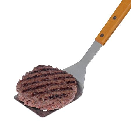 Grilled hamburger on a bargecue spatula isolated on white Imagens