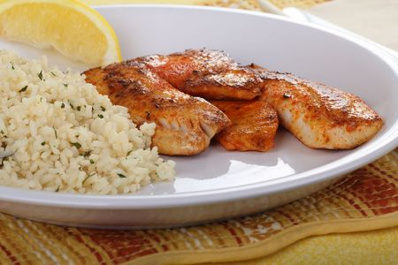 Tilapia fish fillets with rice and a slice of lemon