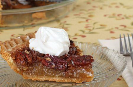 pecan pie: Rebanada de pastel de pacanas cubierto con crema batida  Foto de archivo