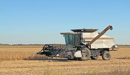 Combine in a farm field harvesting soybeans with a clear blue sky Stock Photo - 8038225