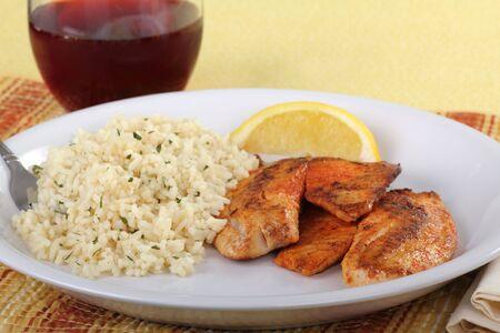Tilapia vis filets diner met rijst, een citroen segment en een drankje  Stockfoto
