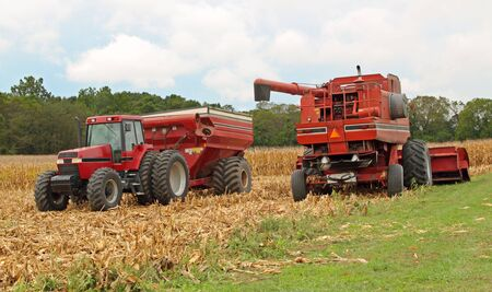 Farm combine and a tractor and wagon harvesting corn photo