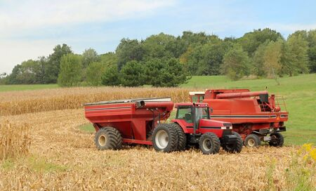 machinery: Red combine and tractor with a wagon harvesting corn