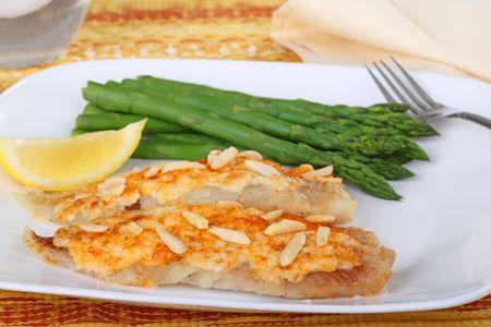 Vis filets gegarneerd met krab vlees saus en amandel lonten met asperges en schijfje citroen Stockfoto