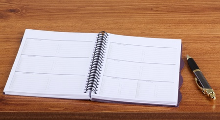Opened weekly planner on a desk with a pen