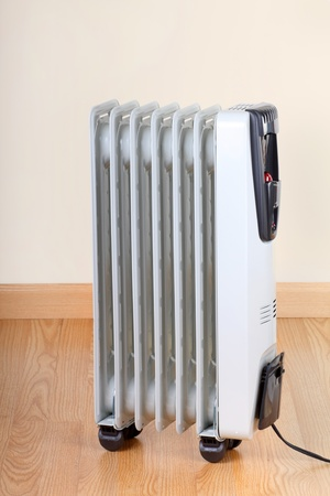 warmth: Electric radiator room space heater on a wood floor