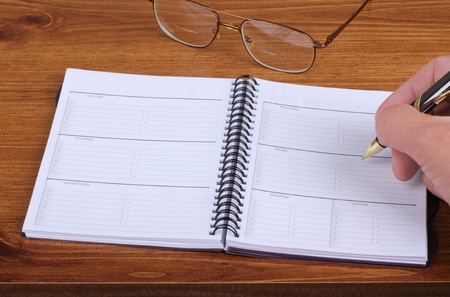 Writing in an opened weekly planner on a desk