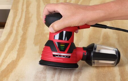 Electric circular sander sanding a piece of plywood Stock Photo
