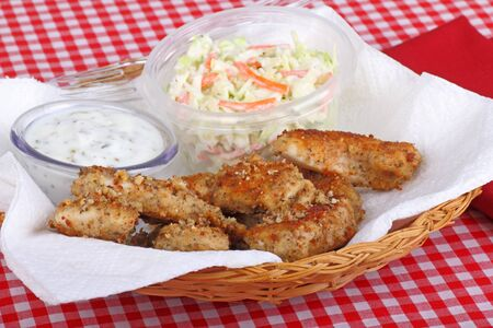 Breaded chicken strips with coleslaw and dipping sauce in a basket Stock Photo