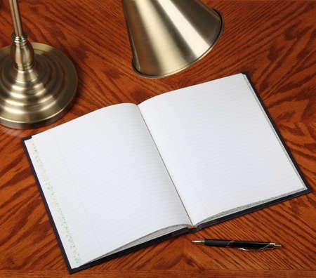 Geopende notebook op een bureau met lamp en pen Stockfoto