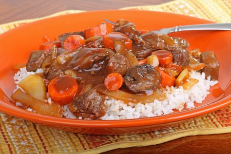 Beef stew with carrots and mushrooms ontop of rice Stock fotó