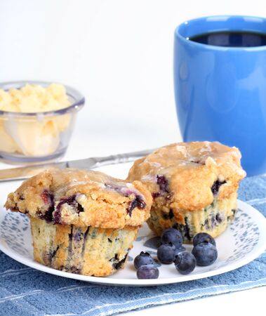 Two blueberry muffins with blueberries on a plate and cup of coffee
