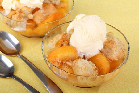 cobbler: Two bowls of peach cobbler with ice cream on top