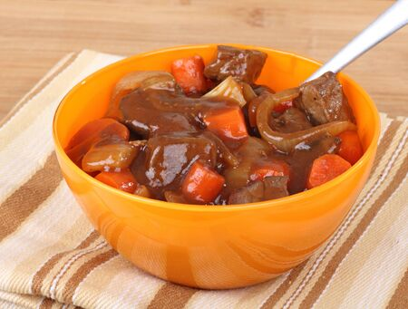 Bowl of beef stew with carrots and onions