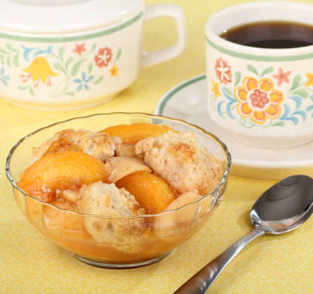 cobbler: Peach cobbler in a bowl with a cup of coffee Stock Photo
