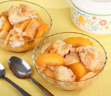 cobbler: Two glass bowls of peach cobbler and spoons Stock Photo